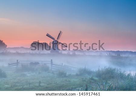 Dutch windmill in dense morning fog at summer sunrise - stock photo
