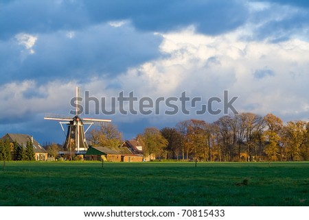 Dutch windmill lighted by the sun on a stormy Autumn afternoon - stock photo