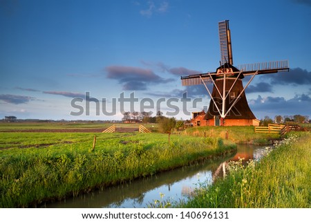 Dutch windmill reflected in river in morning sunrise sunlight,  Holland - stock photo