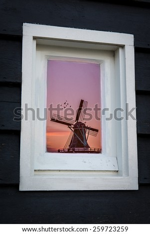 Dutch windmill reflection in window during sunset - stock photo