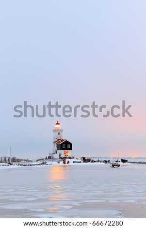Dutch winter landscape with frozen sea and lighthouse - stock photo