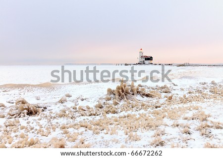Dutch winter landscape with frozen sea and lighthouse, Marken, the Netherlands - stock photo