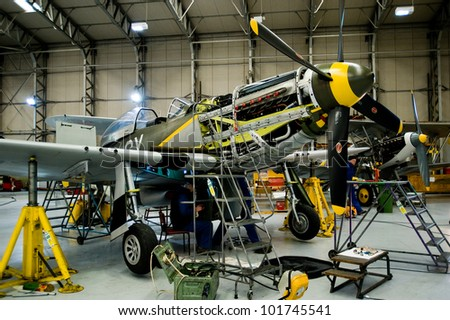 DUXFORD, UK - CIRCA MARCH 2009: Workers maintain the historic fighter planes of World War II circa March 2009 in Duxford, UK. - stock photo