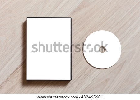 Dvd or cd disc cover case mockup. Template with plastic box and disc with white isolated free space for design. Mock up with black package for compact or dvd disc. On wooden table background - stock photo