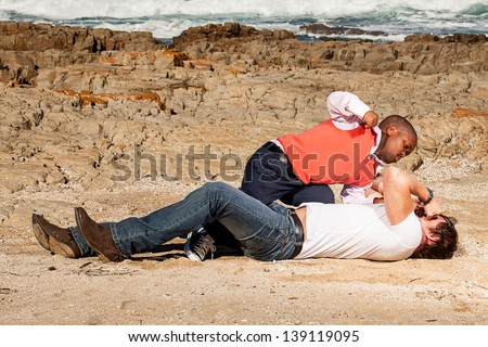 dwarfish african man hitting an young caucasian man with a fist in the sand - stock photo