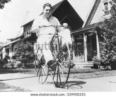 Dwight Hardwick riding a hand made bicycle built by his grandfather in Minnesota in 1838. It is peddled on the front wheel and made with ordinary buggy wheels. Seattle, Washington, June 16, 1934 - stock photo