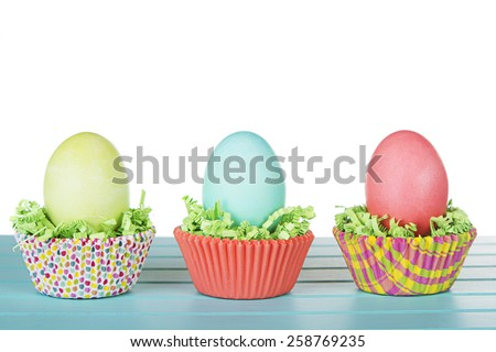 Dyed Easter eggs in a nest of green grass confetti and cup cake wrappers, on a turquoise blue wood panel - stock photo