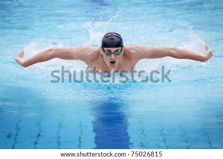 dynamic and fit swimmer in cap breathing performing the butterfly stroke - stock photo