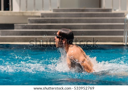 Dynamic and fit swimmer taking a deep breath in the pool