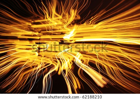 Dynamic glowing yellow lines on dark background - stock photo