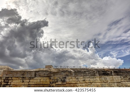 Dynamic HDR photo of cloudy skies and sun behind the clouds and historic city Valletta
