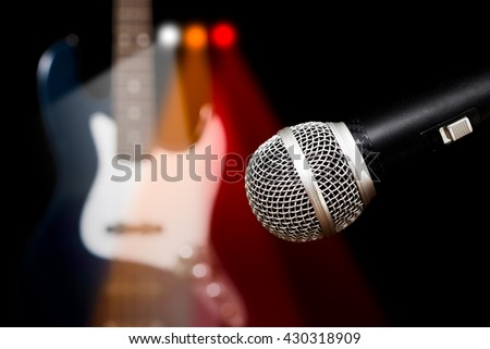 dynamic microphone & bass guitar with colorful spotlight, isolated on black for music concept - stock photo