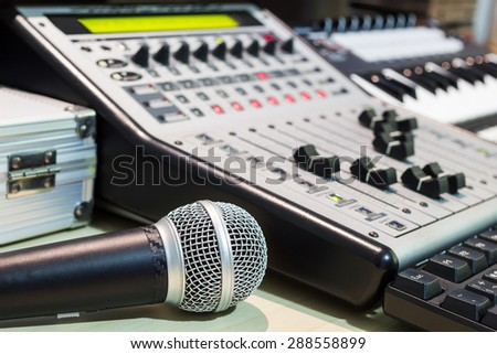 dynamic microphone, digital studio mixer & keyboard synthesizer, focus on mic for music recording, radio / tv broadcasting background - stock photo