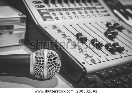 dynamic microphone, digital studio mixer & keyboard synthesizer, focus to mic / B&W processed for music recording, radio / tv broadcasting  background - stock photo