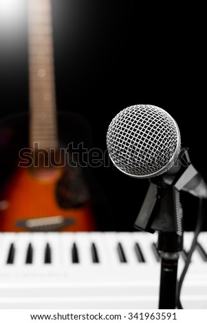 dynamic microphone, piano and acoustic guitar isolated on black - stock photo