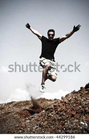 Dynamic Photo Of A Young Man Jumping On A Hill - stock photo
