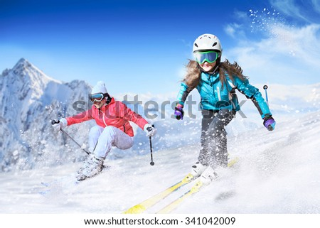 Dynamic picture of a skier and snowboarder on the piste in Alps - stock photo