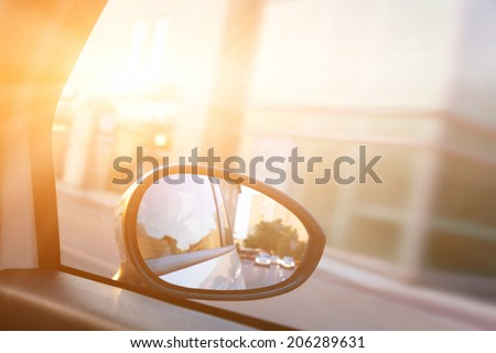 Dynamic view from car on the wing mirror during drive. Sun shining. Transportation, travel, speed. - stock photo