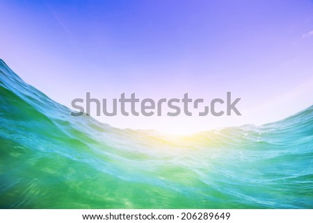 Dynamic water wave in the ocean. View from the waterline. Underwater and blue sunny sky. - stock photo