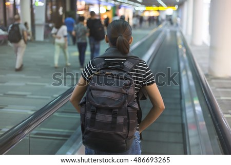Dynamic woman traveling with backpack at airport make her way to the gate