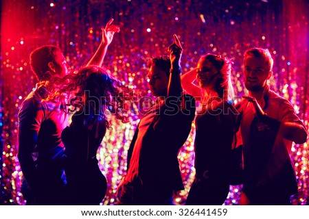 Dynamic young friends dancing at disco party - stock photo
