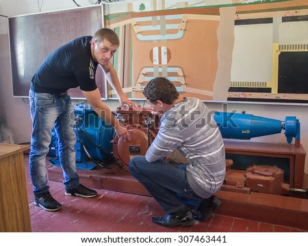 Dzerzhinsk, Ukraine - September 14, 2012: Student and teacher at the technical college lab to study the mining equipment - stock photo