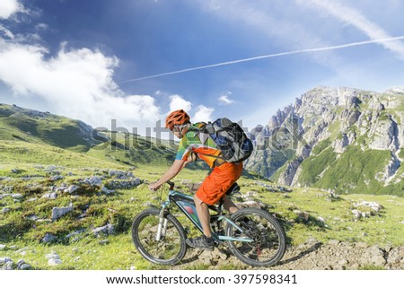 E bike traveler with backpack rides a mountain trail - stock photo