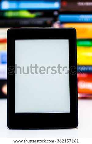 E-book reader on background of old books - stock photo