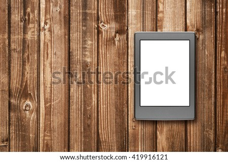 E-book reader on wooden background - stock photo
