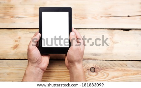 E-book reader or tablet pc in hand. Wood background - stock photo