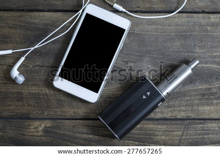 E-cigarette and phone on table, from above - stock photo
