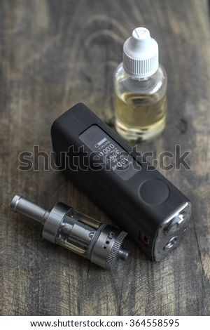E-cigarette or vaping device on wooden surface, natural light - stock photo