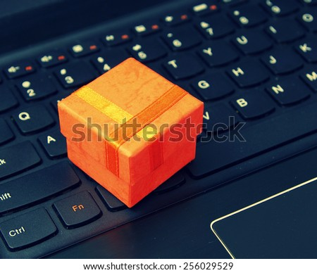 e-commerce and web shopping: orange present case on the laptop keyboard - instagram style - stock photo