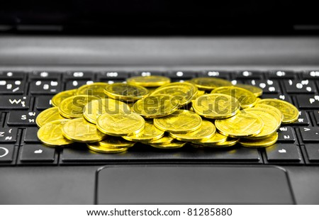 E-commerce concept with Gold Coil and laptop isolated on the white - stock photo