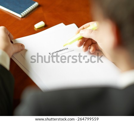E-commerce definition as a shallow depth of field close-up composition of a man in a business suit working with the text
