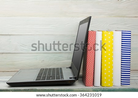E-learning concept. Digital library - books inside laptop. Copy space for text - stock photo