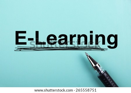 E-learning text is on blue paper with black ball-point pen aside. - stock photo