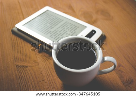 e-Reader and cup of coffee on wooden table - stock photo