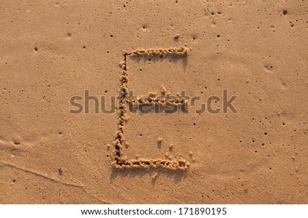 E text written in the sandy on the beach - stock photo