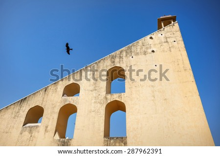 Eagle flying near Jantar Mantar observatory complex at blue sky in Jaipur, Rajasthan, India