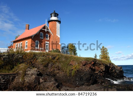 Eagle Harbor Lighthouse is perched on a rocky cliff above Lake Superior.  House and light are of the same brick architeture and joined as one. - stock photo