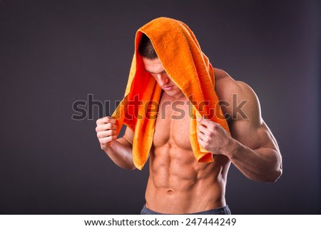 ealthy muscular young man after a workout on dark background.Fitness man holding a orange  towel against dark background.Strong Athletic Man Fitness Model Torso showing  abs. holding towel. - stock photo
