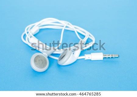ear buds or earphones on blue background