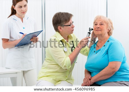 Ear examination. ENT physician looking into patient's ear with an instrument - stock photo