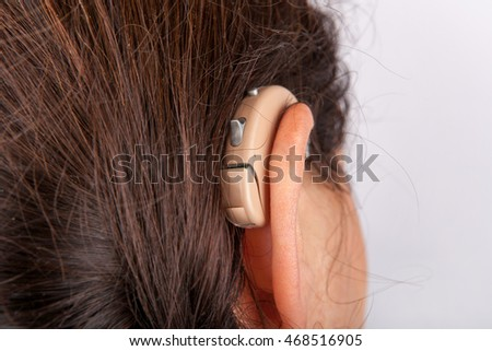 Ear of a woman close-up with a hearing aid