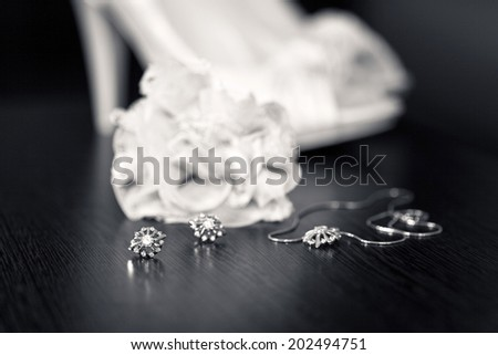 Earings and necklace with bride's bouquet and shoes - stock photo