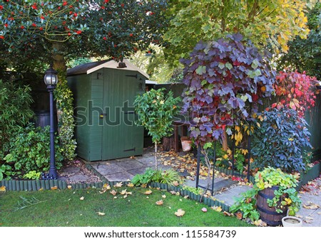 Early Autumn in an English  garden with shed and lamp post - stock photo