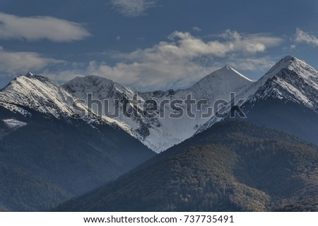 Early autumn snow in Carpathian Mountains: huge cliffs are covered with snow, in the foreground are slopes with forest. View of Fagaras Mountains near Moldoveanu, the highest mountain peak in Romania.