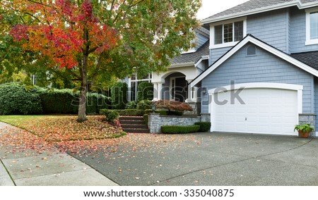 Early autumn with modern residential single family home. View from Drive towards front of house.  - stock photo