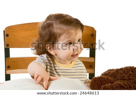 Early development series - baby boy with thoughtful inquiring facial expression sitting at school desk with toy and book on it. He looks away from camera and pointing his finger to textbook - stock photo